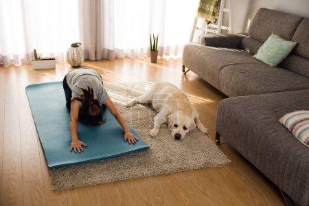 woman doing yoga exercise with dog