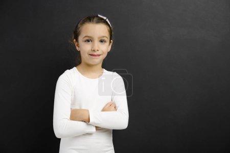 girl smiling in front of blackboard