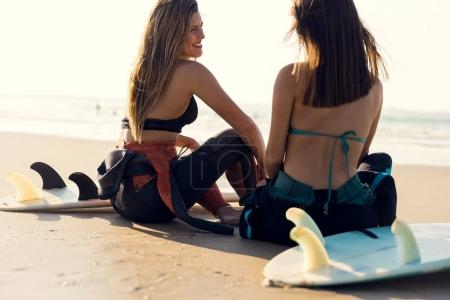Two beautiful young women sitting on beach sand with surfboards looking at ocean