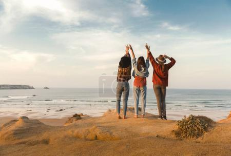 Photo for Three best friends near coastline looking to wavy sea - Royalty Free Image