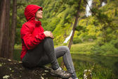 Woman in red coat sitting in green forest