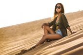 Young woman sitting on sand dune