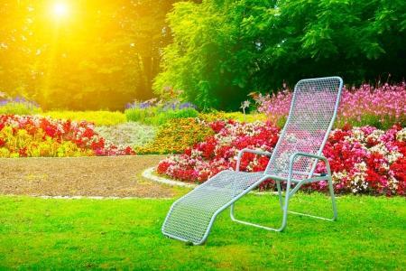 Photo pour Transat dans le parc prochain lit de fleurs à l'aube - image libre de droit