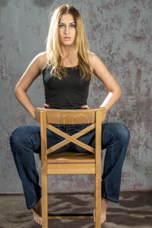 Young slender blonde girl in jeans and shirt posing coquettishly