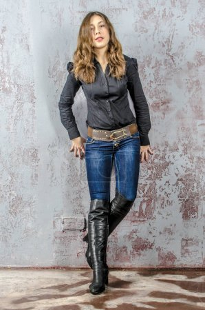 Photo for Young girl with curly hair in a black shirt, jeans and high boots cowboy western style - Royalty Free Image