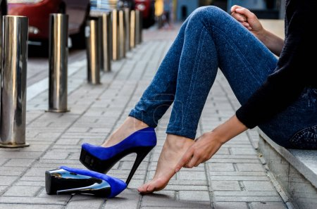 Slender female feet in inconvenient, painful blue high-heeled sh