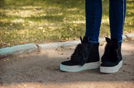Jambes fines en jeans chaussées de bottes tendance avec fourrure et oreilles sur un