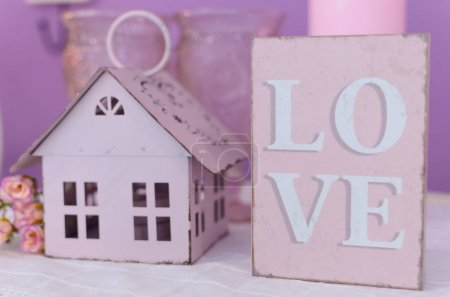 """Photo for Home Sweet Home. Postcard of a cozy cute house. The tablet """"Love"""" and a candlestick in the form of a house - Royalty Free Image"""