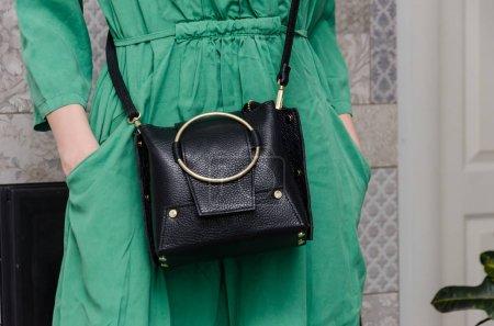 Photo pour Femme élégante avec une femme à la mode a un petit sac noir (embrayage) avec un grand anneau en métal d'or. Hit la saison, une chose super cool pour l'été . - image libre de droit