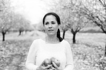 Photo for Outdoor portrait of mature woman holding red apples - Royalty Free Image