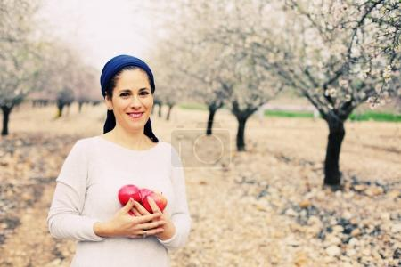 mature woman holding red apples