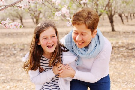 mother and daughter in blooming park