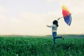 girl with umbrella  jumping in field