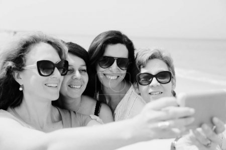 Portrait of four  40 years old women on seaside