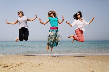 Foto de Retrato de tres mujeres maduras divirtiéndose en la playa - Imagen libre de derechos
