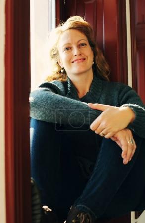 mature woman sitting near window