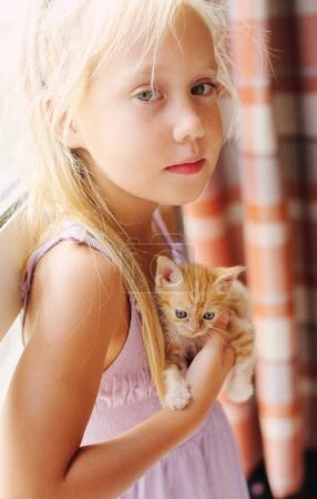 little girl with red kitten