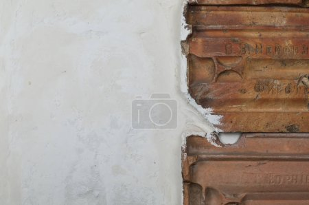 Detail of white grungy wall texture with roof tiles stucco walls and vintage red tiles