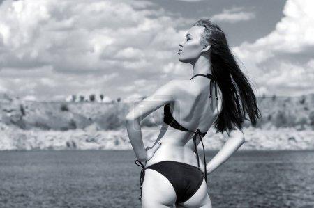 Photo pour Belle fille brune sexy posant en maillot de bain sur la rive rocheuse du lac - image libre de droit