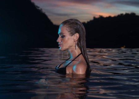 Beautiful sensual woman alone in infinity swimming pool
