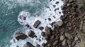 Aerial top view of sea waves hitting rocks on the beach in Phuket