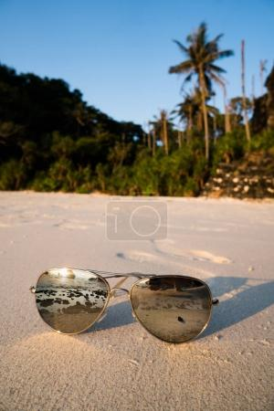 Photo for Closeup sunglasses on sandy beach over beautiful summer blue sky and tropical island background - Royalty Free Image
