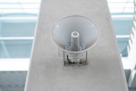 Old loud speaker on white cement pillar