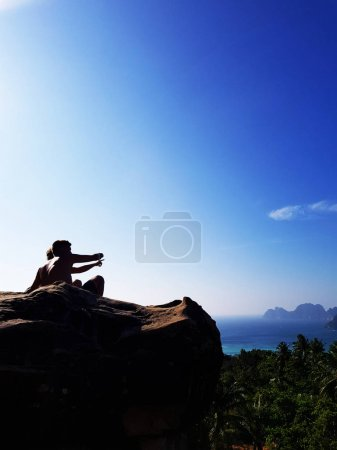 Silhouette couple sitting on the top of mountain over blue sea and sky background