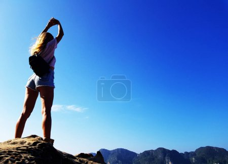 Silhouette woman standing on the top of mountain over blue sea and sky background