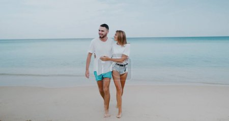 Beautiful happy couple walking on tropical sandy beach over sea and sky background