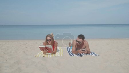 Happy couple relaxing on the sandy tropical beach during sunny summer day