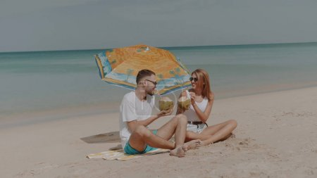 Young happy couple drinking coconut milk on the tropical beach during sunny summer holiday