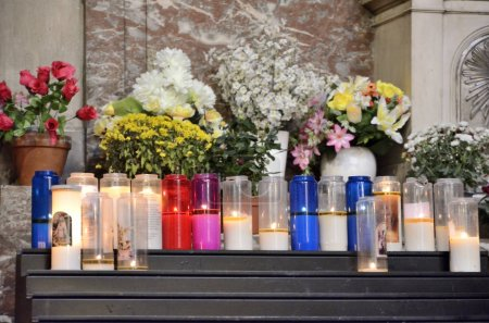 Burning candles and flowers bouquets in a church....
