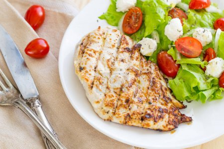 Marinated Grilled Healthy Chicken Breast served with Fresh Salad on a Wooden Background