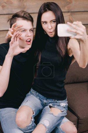 Photo pour Couple romantique ou entre amis jouent l'ape et font selfie photo à la maison sur fond de mur en bois - image libre de droit