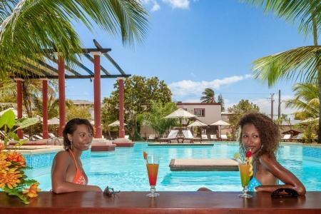 Photo for Two beautiful young Malagasy women drinking cocktails in the swimming pool bar - Royalty Free Image