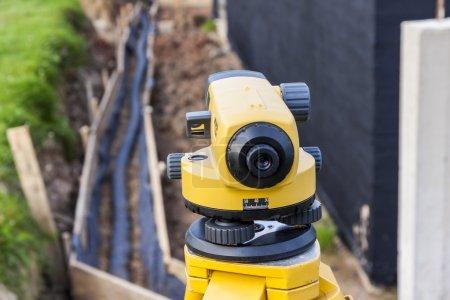 Photo pour Équipement d'arpentage niveau optique sur chantier - image libre de droit