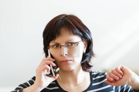 Foto de Hermosa mujer de mediana edad ama de casa cansada sin llamada de maquillaje por teléfono y recibiendo malas noticias - Imagen libre de derechos