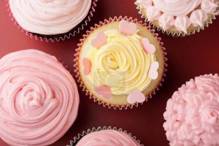 Photo pour Vue du dessus de petits gâteaux avec glaçage rose, fond rouge - image libre de droit