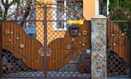wooden gate with beautiful wrought iron elements flowers
