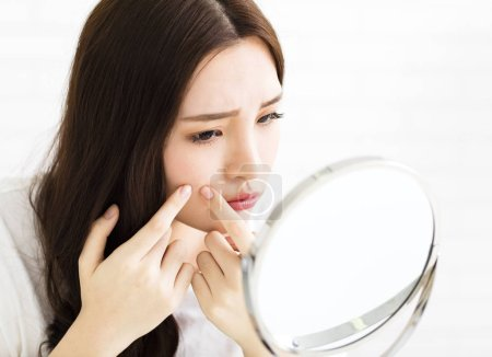 Young woman squeeze her acne in front of the mirror