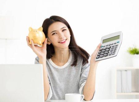 Photo pour Jeune femme montrant calculatrice et tirelire - image libre de droit