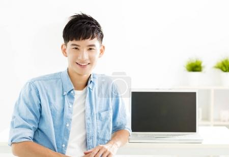 Photo for Smiling asian Young man with laptop - Royalty Free Image