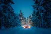 Winter Driving at night - Lights of car in snowy road