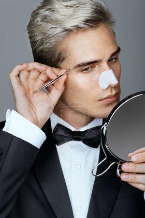 Gentleman concentrating on tweezing his eyebrows.