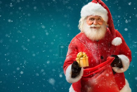 Happy Santa Claus with gift on blue background.