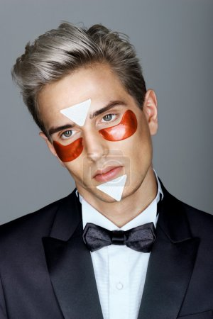 Elegant man with red eye patches