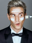 Funny classy man with cream lines on face, spa treatment.