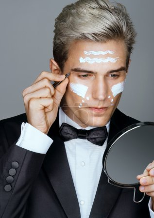 Photo of handsome man tweezing the hair on his face. Wrinkle cream or anti-aging skin care cream.