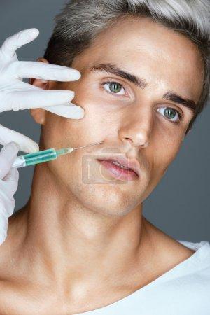 Photo pour Bel homme s'injection de Botox dans les plis naso-labiaux. Cosmétologie. Concept de beauté - image libre de droit